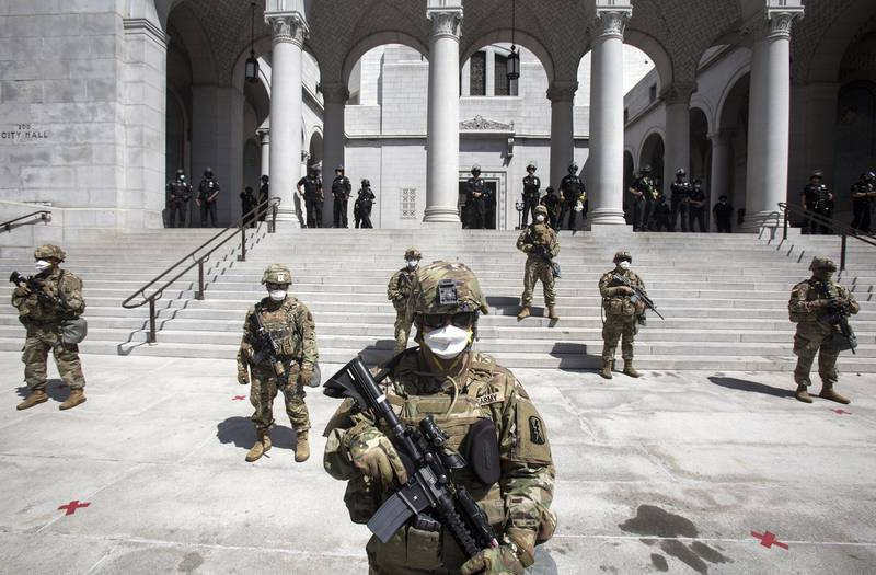 Members of California National Guard stand guard outside the City Hall, Sunday, May 31, 2020, in Los Angeles.