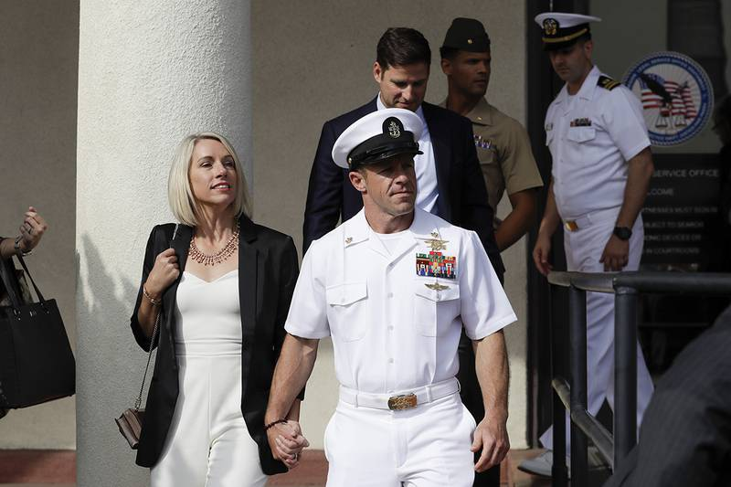 Navy Special Operations Chief Edward Gallagher, center, walks with his wife, Andrea Gallagher, as they leave a military court on Naval Base San Diego, Tuesday, July 2, 2019, in San Diego.