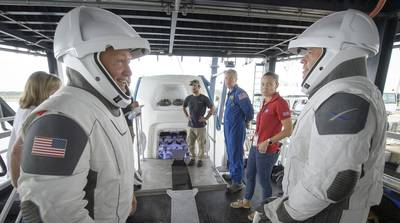 In this Aug. 13, 2019, file photo, NASA astronauts Doug Hurley, left, and Bob Behnken work with teams from NASA and SpaceX to rehearse crew extraction from SpaceX's Crew Dragon at the Trident Basin in Cape Canaveral, Fla.
