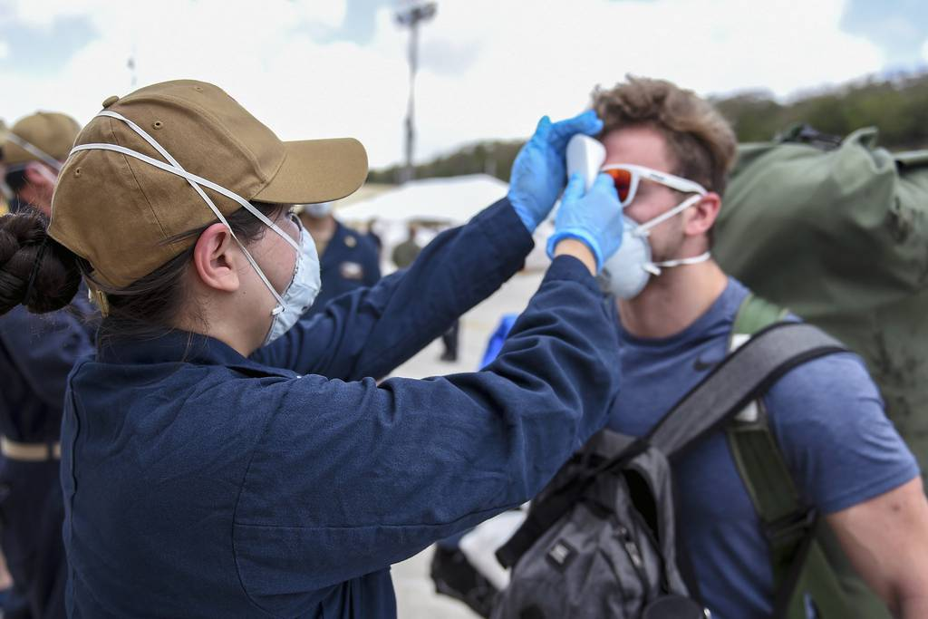 Sailors assigned to the aircraft carrier Theodore Roosevelt (CVN 71), who have tested negative twice for COVID-19 and are asymptomatic, arrive pierside and prepare to return to the ship on April 30, 2020, following completion of their off-ship quarantine at Naval Base Guam