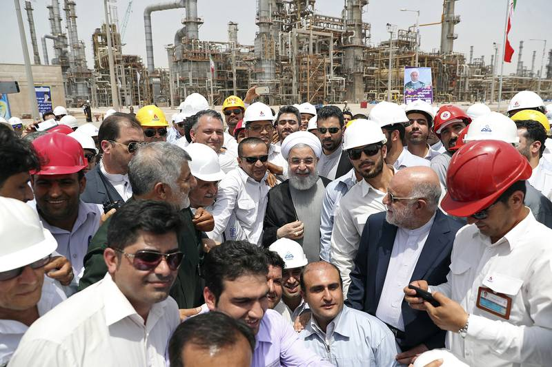 In this April 30, 2017, file photo, released by an official website of the office of the Iranian Presidency, Iranian President Hassan Rouhani, center, inaugurates the Persian Gulf Star Refinery in Bandar Abbas, Iran.