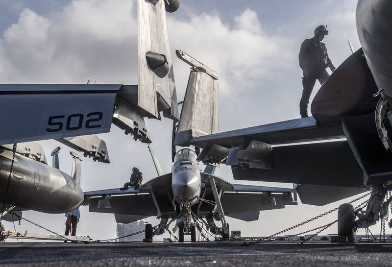 Sailors perform F/A-18 turnaround inspections Dec. 29, 2020, on the flight deck of the aircraft carrier USS Nimitz (CVN 68) in the Indian Ocean.