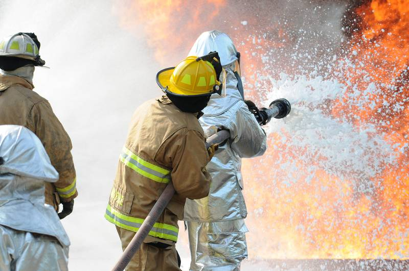 U.S. Air Force and New Jersey state fire protection specialists from the New Jersey Air National Guard's 177th Fighter Wing battle a simulated aircraft fire with Aqueous Film Forming Foam at Military Sealift Command Training Center East in Freehold, N.J., on June 12, 2015.