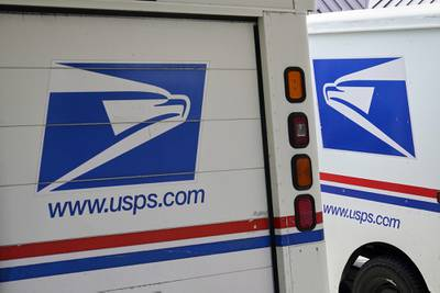 In this Aug. 18, 2020, file photo, mail delivery vehicles are parked outside a post office in Boys Town, Neb.