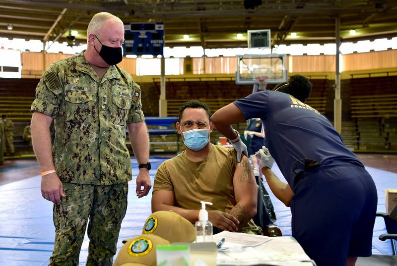 Master-at-Arms 1st Class Patrick Moore receives the COVID-19 vaccine as U.S. Pacific Fleet Fleet Master Chief James Honea observes at Joint Base Pearl Harbor-Hickam, Dec. 29, 2020.