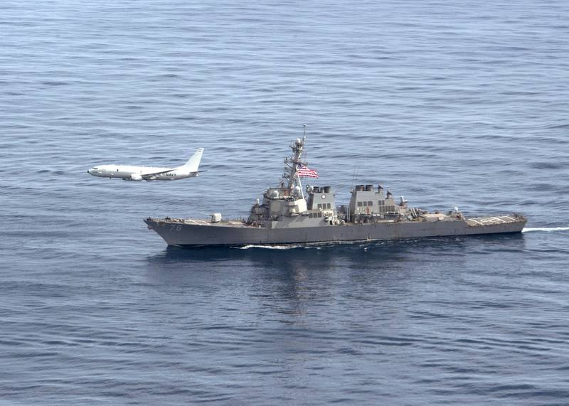 A P-8A Poseidon aircraft flies alongside the Arleigh Burke-class guided-missile destroyer USS Porter (DDG 78) during a photo exercise, March 29, 2020, in the Atlantic Ocean.