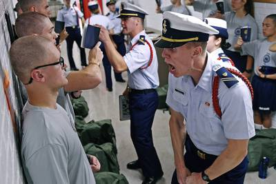 In this July 1, 2019, file photo, Whisky 2 company Cadre Jacob Denns, right, shouts instructions to swab Nicolas Fisher, left, of Pelham, N.H., on the first day of a seven-week indoctrination to military academy life for the Class of 2023 at the U.S. Coast Guard Academy in New London, Conn.