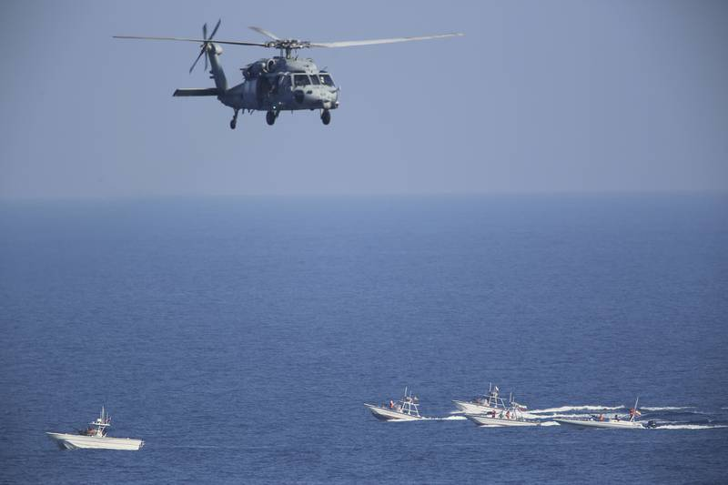 In this Dec. 21, 2018, file photo, a U.S. MH-60 Seahawk helicopter flies over Iranian Revolutionary Guard patrol boats in the Strait of Hormuz.