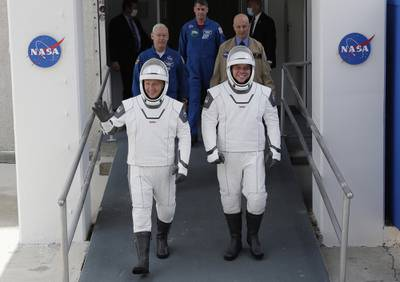 NASA astronauts Douglas Hurley, left, and Robert Behnken wave as they walk out of the Neil A. Armstrong Operations and Checkout Building on their way to Pad 39-A, at the Kennedy Space Center in Cape Canaveral, Fla., Wednesday, May 27, 2020.