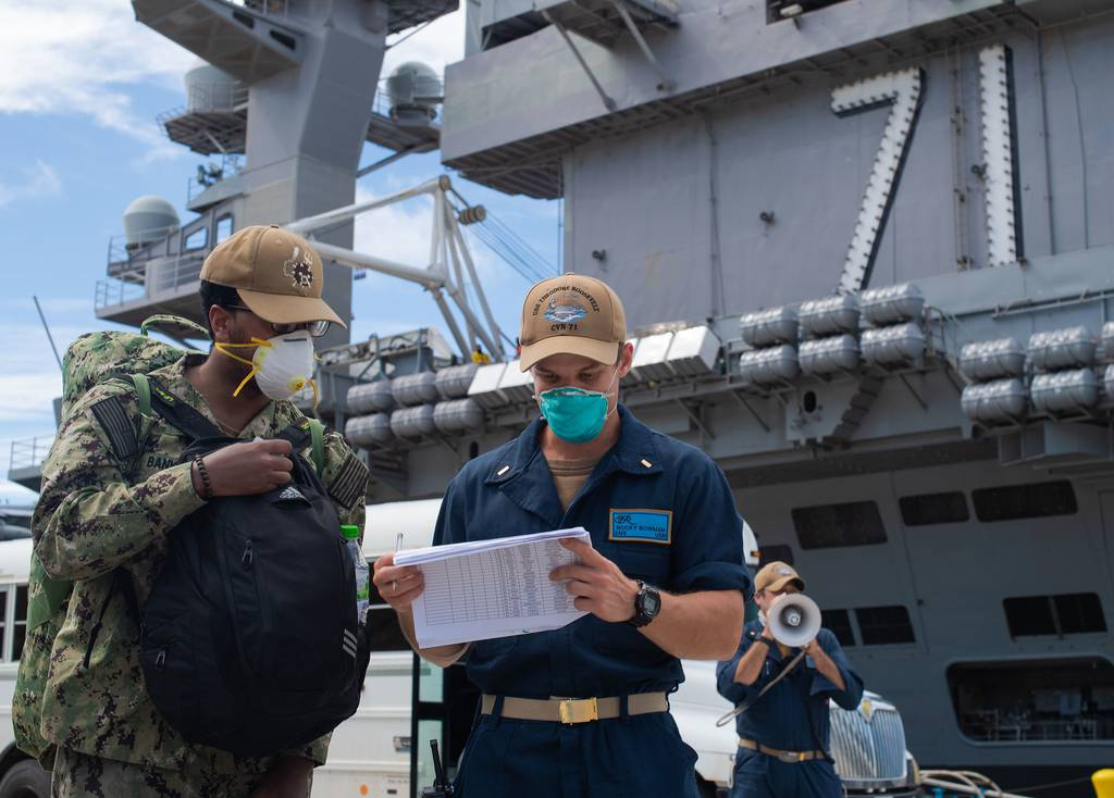 Ensign Rocky Bowman, right, checks Aviation Structural Mechanic 2nd Class Justin Banks into the aircraft carrier USS Theodore Roosevelt (CVN 71) May 16, 2020, after Banks completed off-base quarantine.
