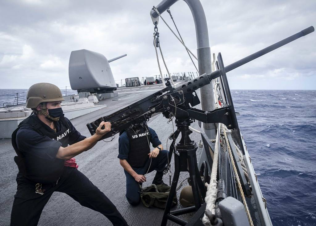 """Fire Controlman 2nd Class Samuel Thomas """"racks"""" an M2HB .50-caliber machine gun on the foc's'le during a small craft attack team drill aboard the Arleigh Burke-class guided-missile destroyer USS John S. McCain (DDG 56) on Oct. 7, 2020, in the South China Sea."""