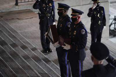 An honor guard carries an urn with the cremated remains of U.S. Capitol Police officer Brian Sicknick and folded flag up the steps of the U.S Capitol to lie in honor in the Rotunda, Tuesday, Feb. 2, 2021, in Washington.