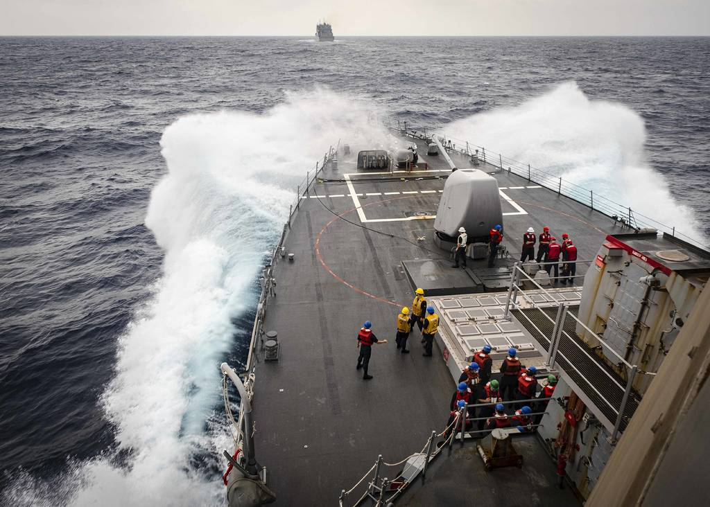 Sailors observe from the foc's'le as the Arleigh Burke-class guided-missile destroyer USS John S. McCain (DDG 56) makes its approach towards the dry cargo and ammunition ship USNS Alan Shepard (T-AKE 3) prior to a replenishment-at-sea on Oct. 22, 2020, in the South China Sea.