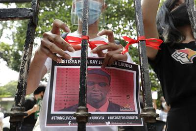 A demonstrator ties a red ribbon on a gate of the Department of Justice to symbolize their protest while holding a picture of U.S. Marine Lance Cpl. Joseph Scott Pemberton during a rally in Manila, Philippines, on Thursday, Sept. 3, 2020.