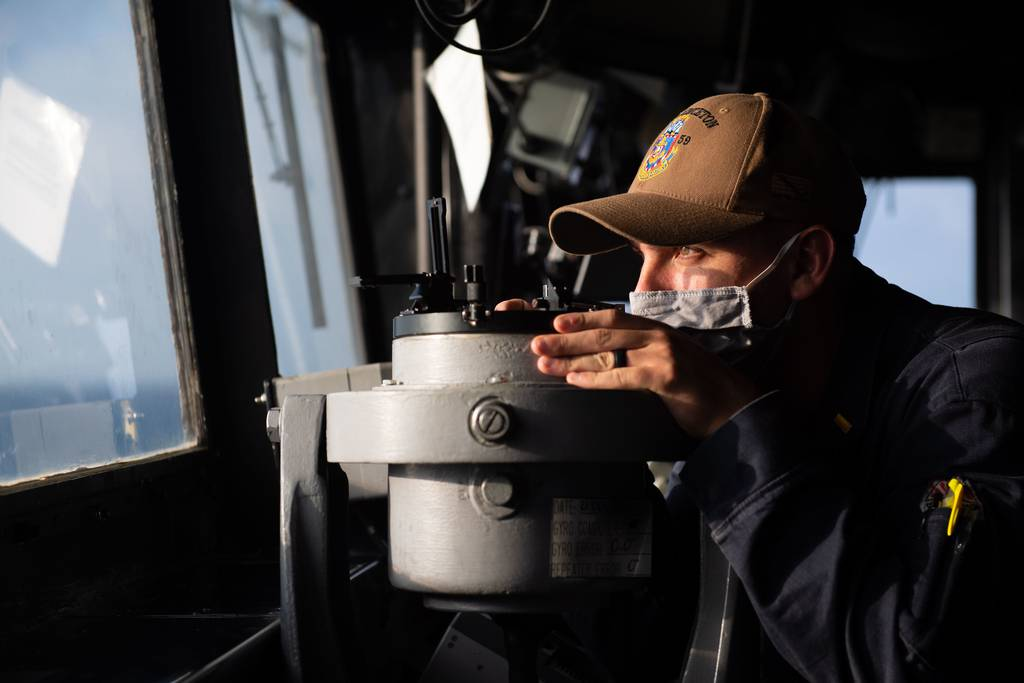 Ensign Chris Luna takes a navigational bearing while standing watch in the pilot house of the guided-missile cruiser USS Princeton (CG 59) on Dec. 21, 2020, in the Indian Ocean.