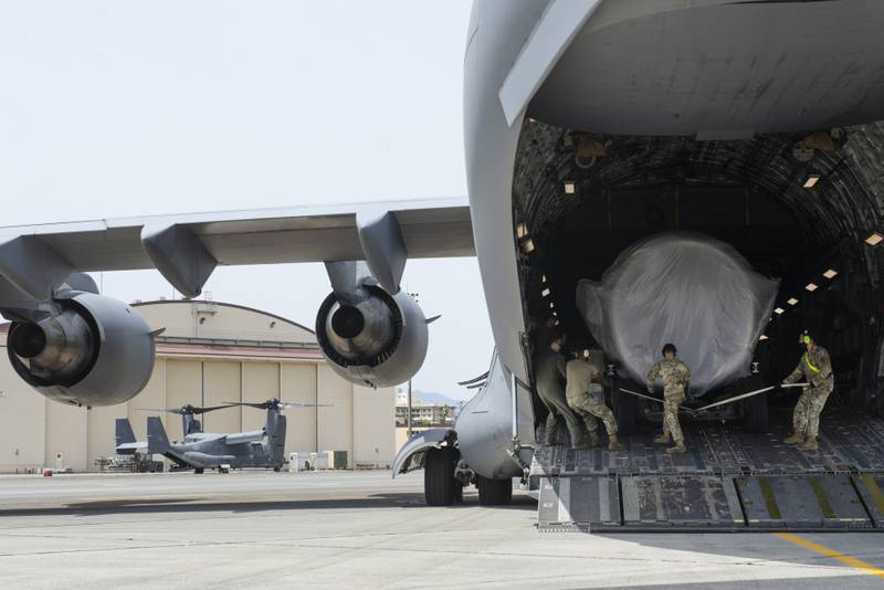 Airmen assigned to the 730th Air Mobility Squadron load a C-17 engine onto a C-17 Globemaster III May, 4, 2021, at Yokota Air Base, Japan. (Tech. Sgt. Christopher Hubenthal/Air Force)