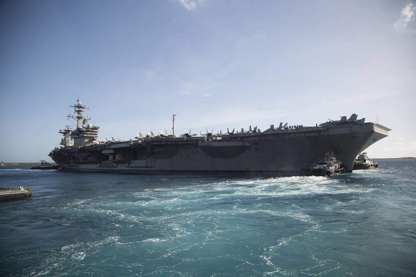 The aircraft carrier USS Theodore Roosevelt (CVN 71) departs Apra Harbor on May 21, 2020, following an extended visit to Guam in the midst of the COVID-19 global pandemic.